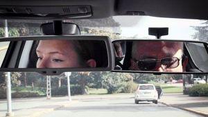Oppilas ja opettaja autokoulun ajotunnilla.