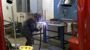 Opiskelija Aalto-yliopiston Taiteiden ja suunnittelun korkeakoulun metallityöpajassa.