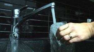 Vettä lasketaan hanasta. Vesi ryöppyää lasin reunan yli.