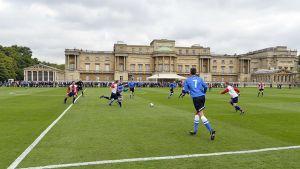 Polytechnic FC ja Civil Service FC pelaamassa jalkapalloa Buckinghamin palatsin puutarhassa.