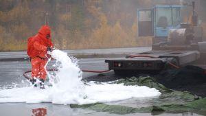 Suojapukuun pukeutunut pelastusmies suihkuttaa vaahtoa maahan.