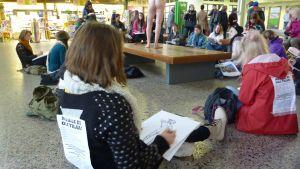Kuvataideopiskelija maalaa alastonmallia Tampereen rautatieasemalla.