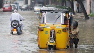 Intialainen riksakuski työntää kulkuvälinettänsä rankkasateen aiheuttamassa tulvavedessä Hyderabadissa.