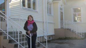 Harjumaan kylätoimikunnan puheenjohtaja Heljä Kontio lakkautettavan kyläkoulun rappusilla.