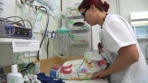 Kätilö hoitaa vastasyntynyttä vauvaa