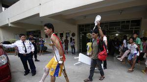 Nuori mies kävelee ulos sairaalasta kainalosauva tukenaan. Hänen ystävänsä kantaa valkoista penkkiä ja tiputuspulloa.