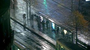 Ihmisiä sateessa raitiovaunupysäkillä.
