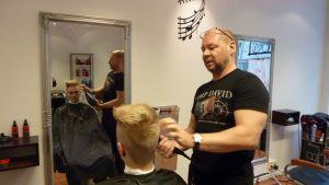Parturi Mika Tirronen kuivaa Santeri Mattilan hiuksia.