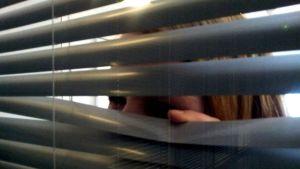 Nainen kurkkii ikkunassa sälekaihdinten takaa
