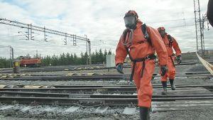 Ensimmäiset onnettomuuspaikalle tulleet palomiehet menevät suojapuvuissa kartoittamaan tilannetta