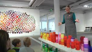 Kuvassa värikkäitä taideteoksia, lapsia kuuntelemassa ja nainen selostamassa