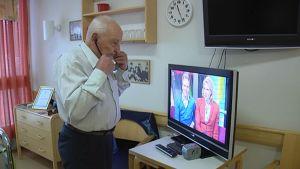 Mies kuuntelee televisiota kuulokojeella
