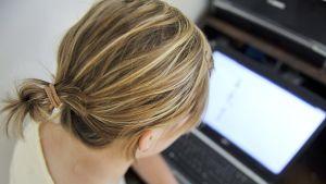 Nuori nainen tietokoneen äärellä.