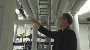 Mies osoittaa putkea Vesi-instituutissa
