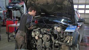 Korjaamossa mies korjaa auton moottoria.