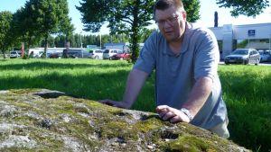 Kuppikivien tutkimista harrastava Jukka Nieminen Hämeenlinnassa Suomen suurimmalla kivellä