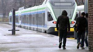 Ihmisiä ja junia rautatieasemalla.