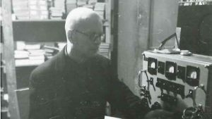 Kuvassa tuntematon mies  radiokaitteen äärellä
