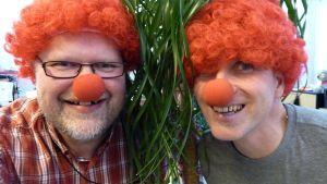 Kaksi miestä punaisissa peruukeissa ja nenissä