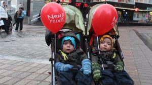 Kaksi lasta rattaissa nenäpäiväilmapallojen kanssa.