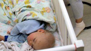 Lapsi nukkumassa pinnasängyssä.
