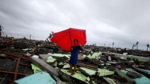 Nainen seisoo sateenvarjo kädessä raunioissa.