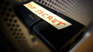 Kuva mustasta muistitikusta, jonka päällä on teksti TOP SECRET.