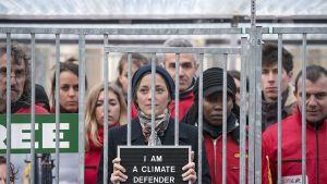 """Ranskalainen näyttelijätär Marion Cotillard seisoo häkissä vierellään punatakkisia ihmisiä. Kädessään hänellä on kyltti, jossa lukee: """"I AM A CLIMATE DEFENDER""""."""