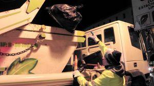 Roskien kuljettaja heittää roskapussia roska-auton lavalle Madridissa.