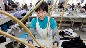 Työntekijä vaatetehtaalla Kiinan Wuzhenissa. Kuva on vuodelta 2008.