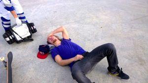 Roope Tonteri makaa loukkaantuneena asvaltin pinnassa.