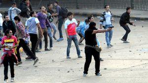 Naamioitunut mielenosoittaja osoittaa pistoolilla.