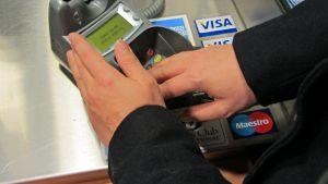 Nainen näppäilee pin-koodinsa maksupäätteelle.
