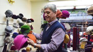 Hattukauppias Pertti Salmela esittelee vintage-hattuja.