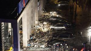 Maxima-kaupan edustalla näkyy romahtaneita rakenteita sekä niiden alle ruhjoutuneita henkilöautoja. Palomiehiä ja muuta pelastushenkilökuntaa kuvan alalaidassa.