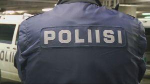 Poliisi-teksti poliisimiehen selässä.