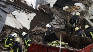 Pelastustyöntekijät raivaavat romahtaneen kauppakeskuksen jäänteitä.