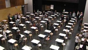 Oppilaat valmistautuvat ylioppilaskirjoituksiin koulun juhlasalissa.