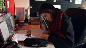 Nuori tyttö tekee läksyjä kirjoituspöydän ääressä