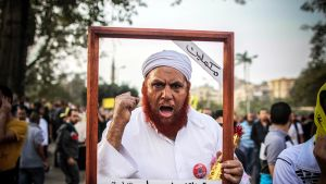 """Muslimiveljeskunnan kannattaja mielenosoituksessa Koubbehin palatsin läheisyydessä Kairossa 29. marraskuuta. Hänen pitelemissään kehyksissä lukee """"Me aiomme jatkaa, valtuudet (armeijalle) on annettu...Eliminointi tapahtuu nyt."""""""