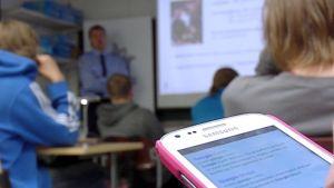 Oppilas selaa kännykkää tunnilla.