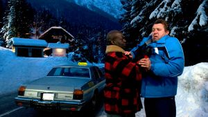 Tumma mies on ottanut Martti Suosalon esittämää henkilöä kauluksista kiinni. Taustalla taksi ja pimenevä vuoristomaisema.