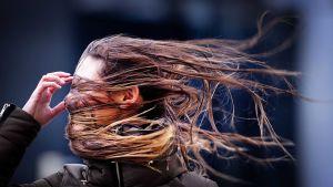 Naisen hiukset omien kasvojen edessä.
