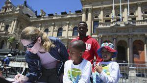 Eteläafrikkalaisia jättämässä surunvalittelujaan Etelä-Afrikan Kapkaupungissa 6. joulukuuta.