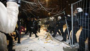 Kiakkovieraiden mielenosoittajat repivät mellakka-aitaa mellakkapoliisien edessä Tampereella 6. joulukuuta.