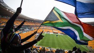 Ihmisiä jalkapallostadionilla Nelson Mandelan muistojuhlassa.