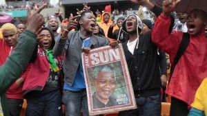 Ihmisiä jalkapallostadionilla Sowetossa vähän ennen Nelson Mandelan muistojuhlan alkamista.
