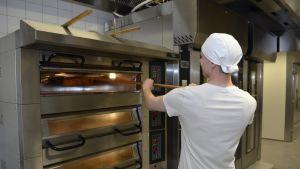 Mies puhdistaa leipäuunia.