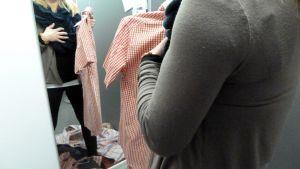 Henkilö sovittaa vaatteita.