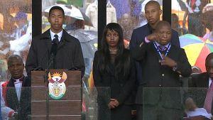 Nelson Mandelan muistojuhlassa puhujalavalla esiintynyt huijariksi paljastunut viittomakielen tulkki oikealla.